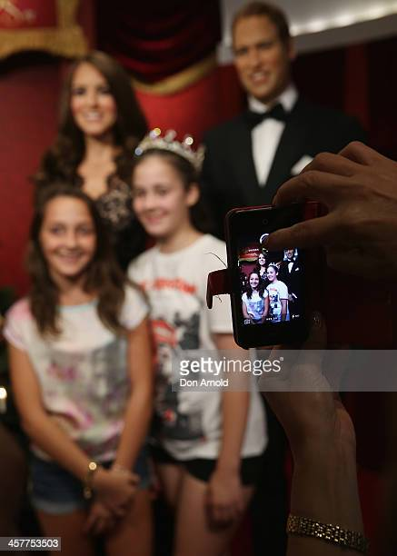 People take photos on their mobile phones of themselves posing alongside wax figures of Princess Catherine and Prince William at Maddam Tussauds on...