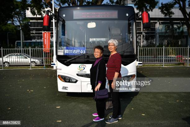 People take photos with the selfdriving bus on December 8 2017 in Shenzhen China The buses have designed speed of 10 to 30 kph Equipped with lidar...