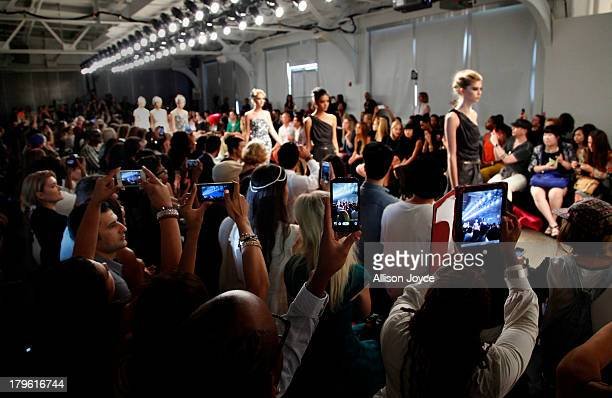 People take photos with their tablets and cell phones during the Fashion Palette Australia fashion show during MercedesBenz Fashion Week Spring 2014...