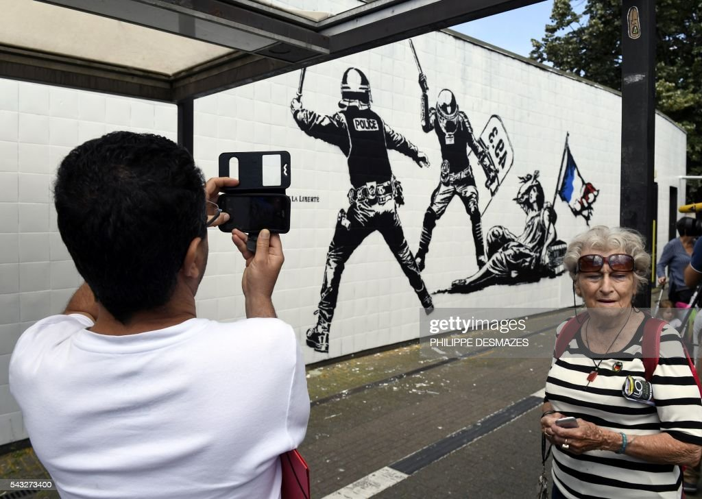 People take picture of a mural by French artist Goin on June 27, 2016 in Grenoble, southeastern France. Mayor of Grenoble Eric Piolle (EELV) Monday invoked the freedom of expression after the controversy surrounding an urban art work deemed 'anti-police,' and created as part of a festival sponsored by the municipality. / AFP / PHILIPPE