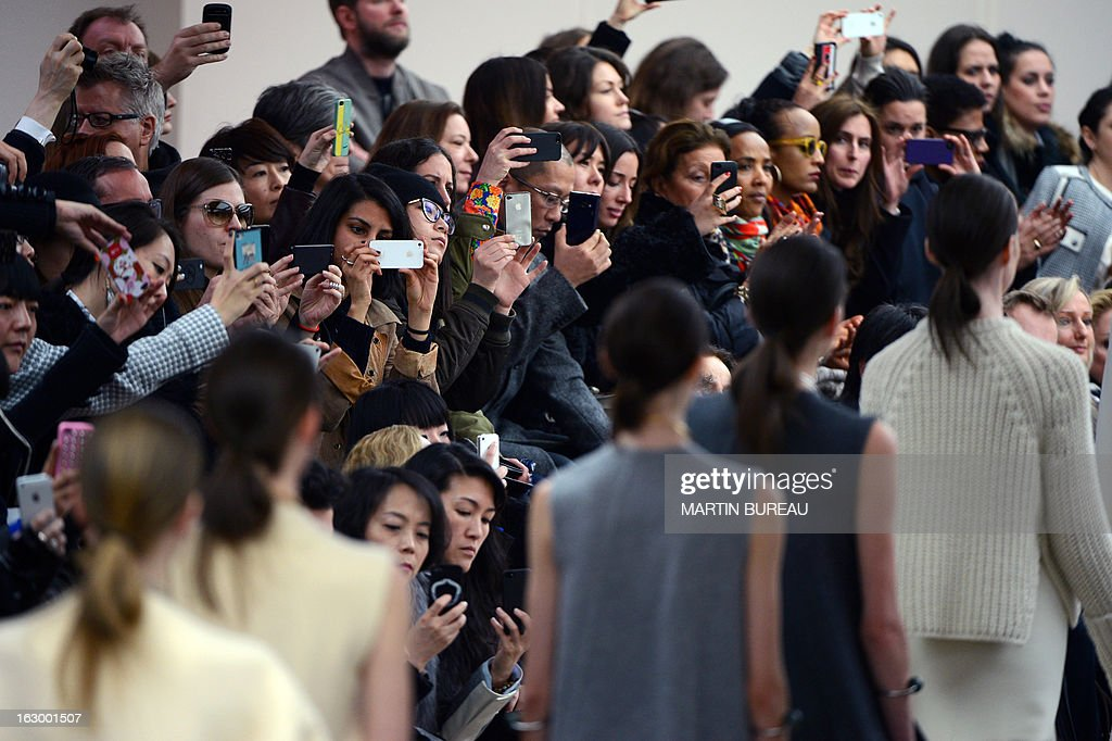 People take picture of models presenting creations for Celine during the Fall/Winter 2013-2014 ready-to-wear collection show, on March 3, 2013 in Paris.