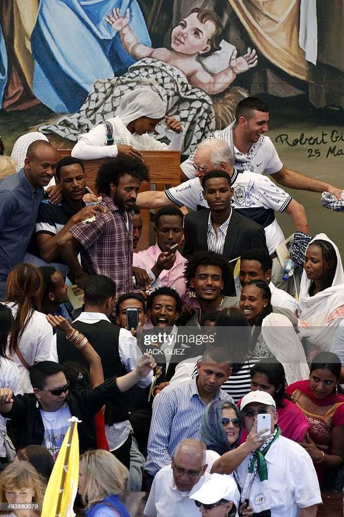 People take pictures and selfies on the stage where Pope Francis led an open-air mass at the Manger Square on May 25, 2014 outside the Church of the Nativity in the West Bank Biblical town of Bethlehem, with a painting of a nativity scene in the background depicting baby Jesus, covered with the trademark Palestinian chequerred kefiyeh. Pope Francis arrived in Bethlehem at the start of the most sensitive part of his three-day Middle East tour aimed at forging regional peace and easing an age-old rift within Christianity. AFP PHOTO / JACK GUEZ