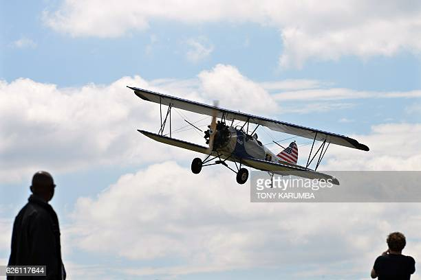 People take pictures and watch a vintage biplane flying at a low altitude over the Nairobi National Park in Nairobi on November 27 2016 as part of of...