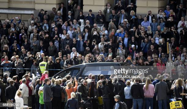 People take pictures as a hearse drives in the funeral procession during a state funeral service for Finland's former President Mauno Koivisto in...