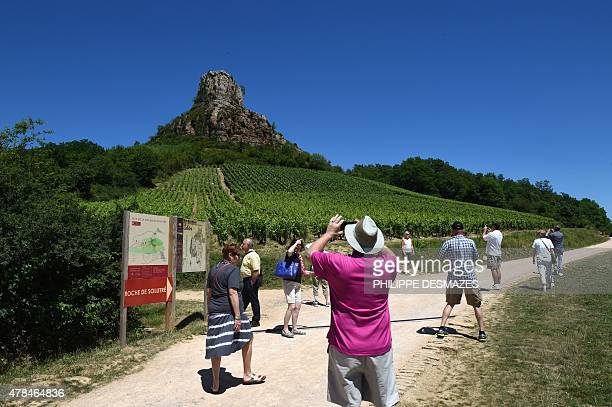 People take pictures as others walk on the hiking path around La Roche de Solutre a limestone escarpment 8 km west of Mâcon overlooking the commune...