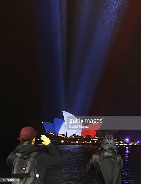 People take pictures as the sails of the Sydney Opera House are illuminated in the colours of the French flag on November 14 2015 in Sydney Australia...