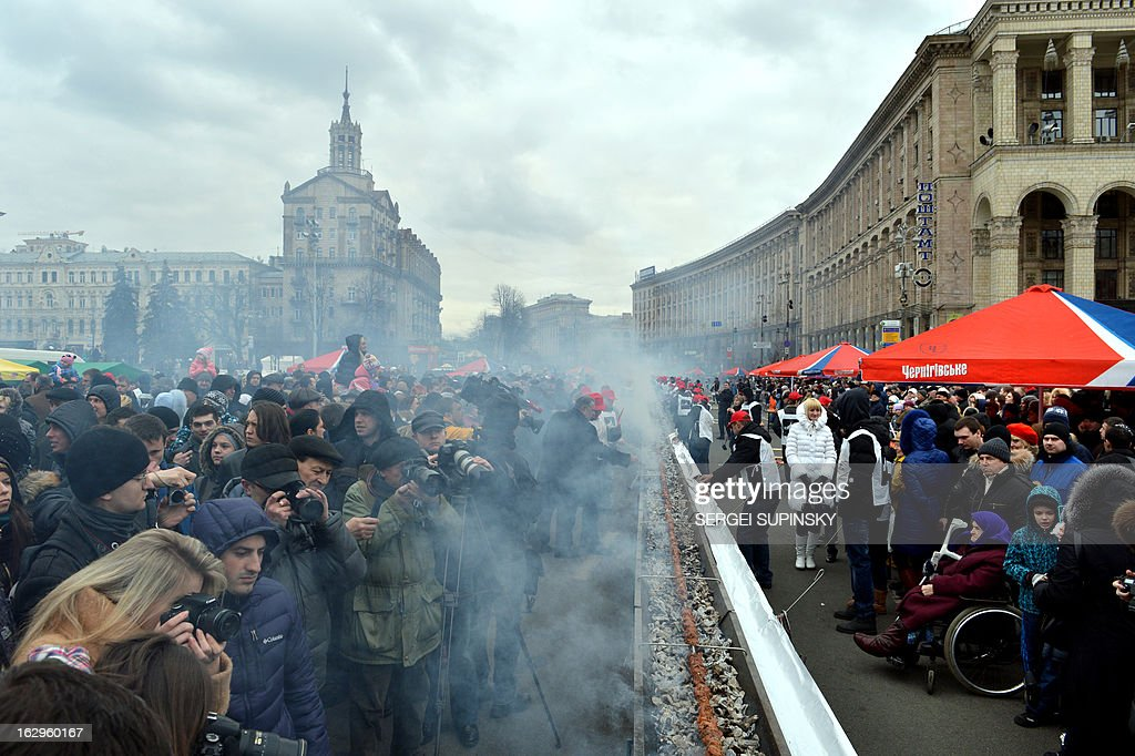 People take pictures as volunteers cook shashlyk, or a skewer of meat, measuring 150.6 meters in length in the Ukrainian capital of Kiev to set a new world record on March 2, 2013. Officials of the Ukrainian National Register of Records fixed the new record for the longest shashlyk, a popular food item throughout the former Soviet Union, Eastern Europe, India, Iran, Mongolia, Morocco, Pakistan and Israel among other places.