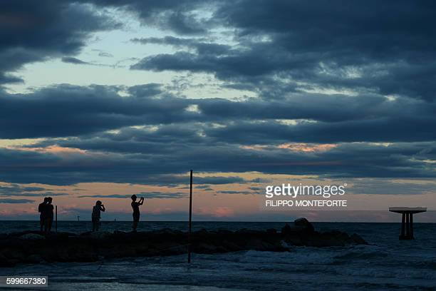 People take pictures at sunset during the 73rd Venice Film Festival on September 6 2016 at Venice Lido / AFP / FILIPPO MONTEFORTE