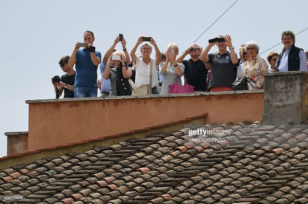 People take pictures from a terrace during a holy mass on the occasion of the Jubilee of Deacons, on May 29, 2016 in Vatican. / AFP / VINCENZO
