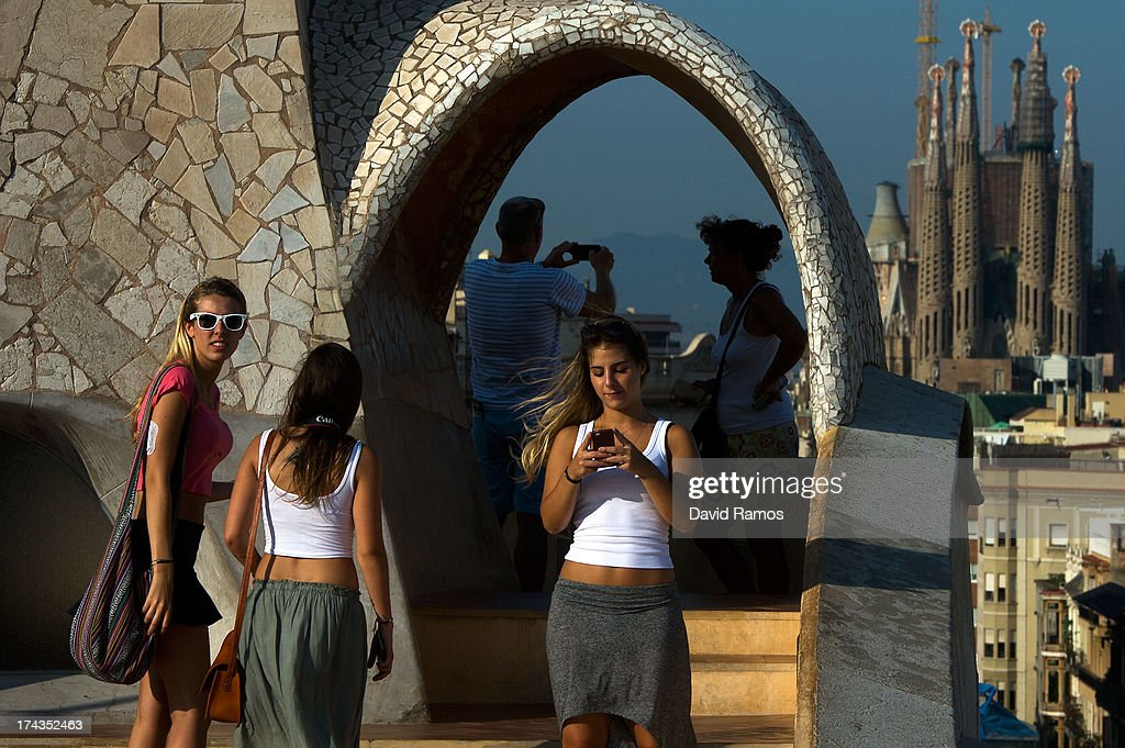 People take pictures from the roof of the building 'La Pedrera' or 'Casa Mila' of Antoni Gaudi with La Sagrada Familia on the background on July 24, 2013 in Barcelona, Spain. Foreign visitors to Spain set a new record high in June surpassing six million tourists for the first time ever and climbing by 5.3 percent since June 2012.