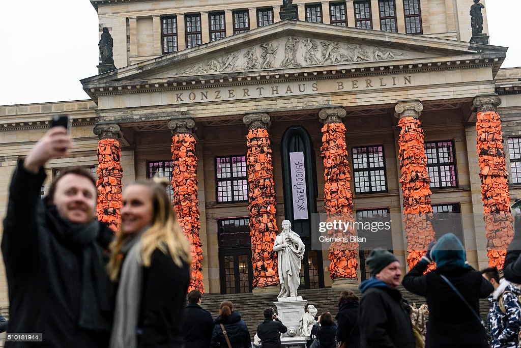 People take pictures in front of an art installation by Chinese artist Ai Weiwei that consists of life vests worn by refugees bound to the columns of the concert house at Gendarmenmarkt on February 14, 2016 in Berlin, Germany. The life vests were among the thousands discarded by migrants and refugees after they crossed the sea from Turkey to Greece. Ai Weiwei lives in Berlin and is currently involved in several projects relating to refugees. Up to 80,000 refugees currently live in Berlin and the city is preparing for the likely arrival of 30,000 more in 2016.