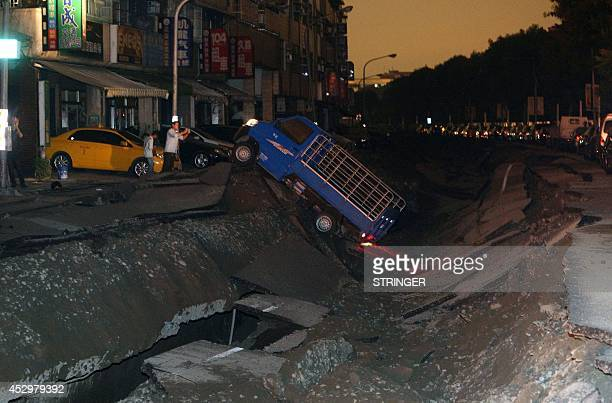 People take pictures of a crater caused by a blast in the city of Kaohsiung in southern Taiwan early on August 1 2014 The explosion that is believed...