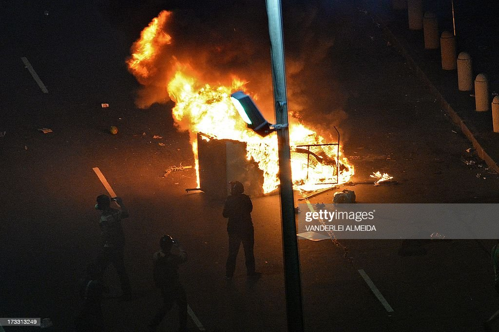 People take pictures of a fire set by demonstrators in the middle of a street after clashes erupted following a march by Brazilian workers in Rio de Janeiro on July 11, 2013 in a day of industrial action called by major unions to press demands for better work conditions. Demonstrators on Thursday blocked roads and staged protest rallies across the country on the 'National Day of Struggles' which was called by the country's five leading labour federations during last month's mass street protests to demand better public services and an end to endemic corruption.