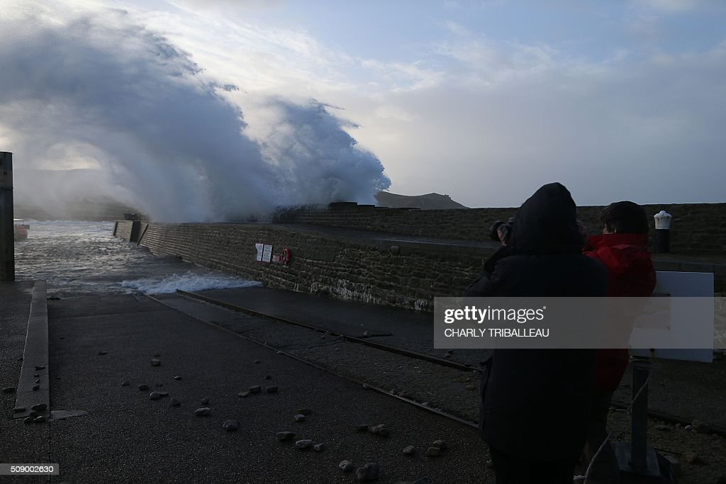 People take pictures of a wave breaking at the harbour in Auderville, northwestern France, on February 8, 2016, as strong winds hit the region. Winds of over 130 kh/h were recorded in the region where 16 departments have been placed under alert for wind and flooding waves. / AFP / CHARLY TRIBALLEAU