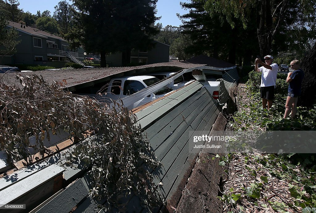 People take pictures of cars crushed under a collapsed carport following a 6.0 earthquake on August 24, 2014 in Napa, California. A 6.0 earthquake rocked the San Francisco Bay Area shortly after 3:00 am on Sunday morning causing damage to buildings and sending at least 70 people to a hospital with non-life threatening injuries.