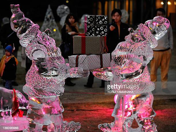 People take pictures of ice statues of Nisse a model of Norwegian Santa Claus at a hotel in Tokyo on December 24 2011 Ice carving championship...