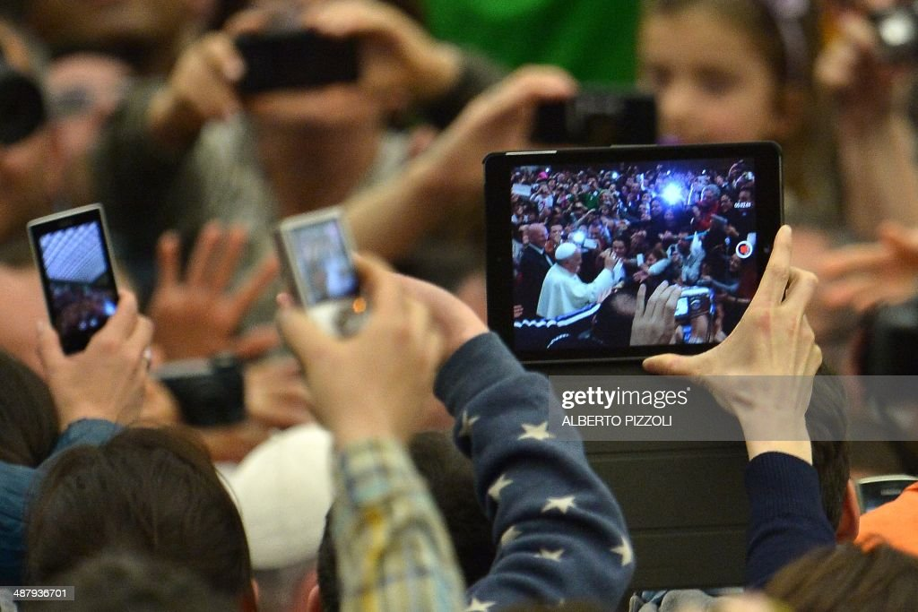 People take pictures of Pope Francis with cameras, mobile phones and tablets during a meeting with members of the Catholic Action at Paul VI audience hall on May 3, 2014 at the Vatican. AFP PHOTO / ALBERTO PIZZOLI
