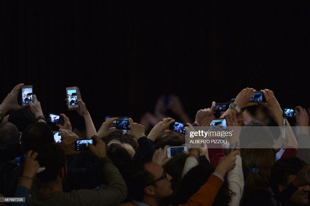 People take pictures of Pope Francis with cameras, mobile phones and tablets during a meeting with members of the Catholic Action at Paul VI audience hall on May 3, 2014 at the Vatican.