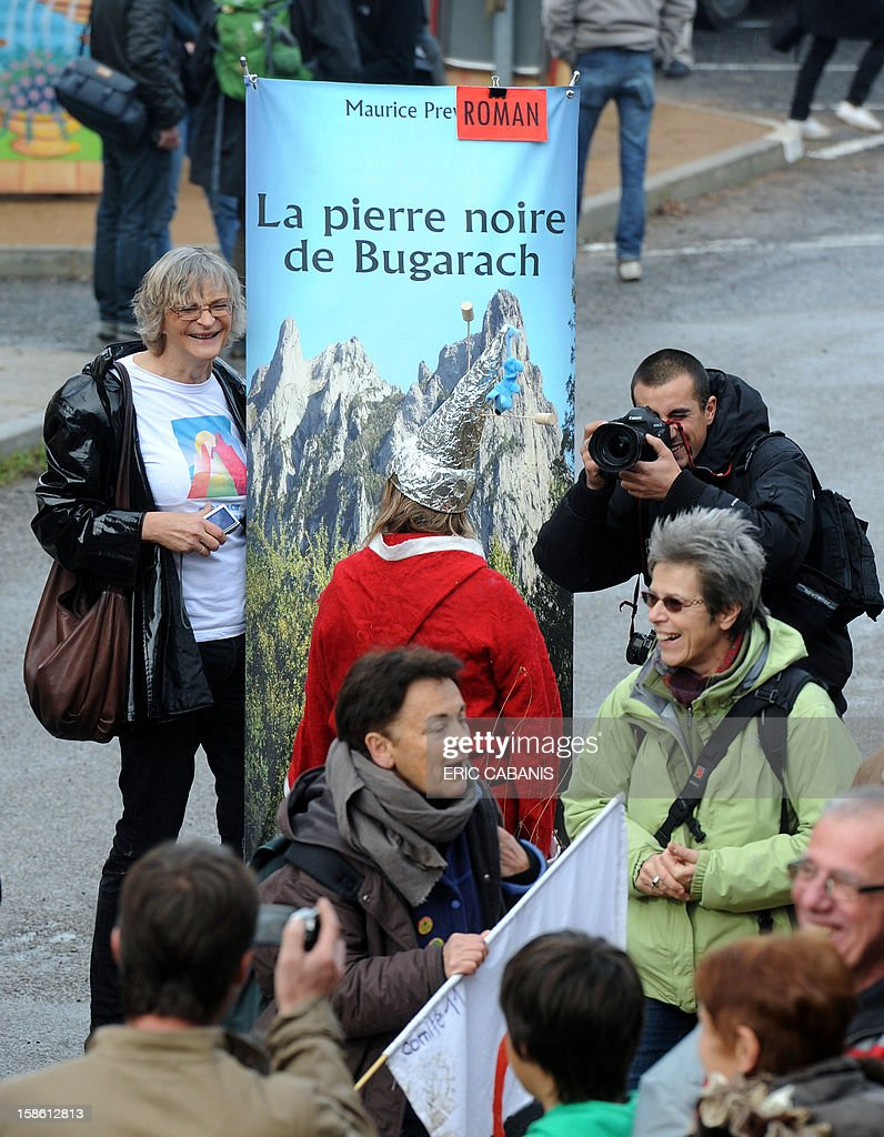 People take pictures of residents of the French southwestern village of Bugarach, on December 21, 2012, near the 1,231 meter high peak of Bugarach - one of the few places on Earth some believe will be spared when the world allegedly ends today according to claims regarding the ancient Mayan calendar. French authorities have pleaded with New Age fanatics, sightseers and media crews not to converge on the tiny village.