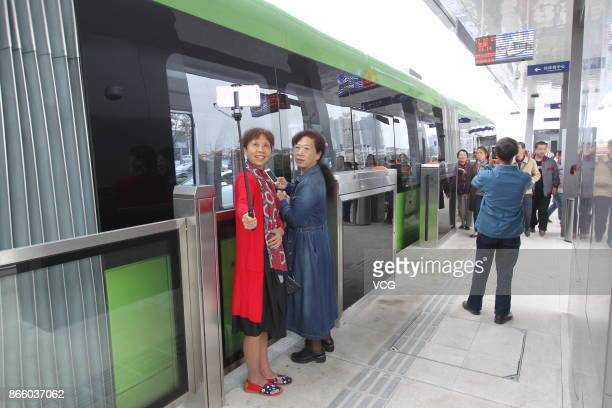 People take pictures of the autonomousrail train during its test run on October 23 2017 in Zhuzhou Hunan Province of China The threecarriage railless...