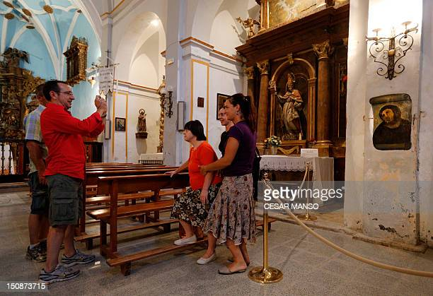People take pictures of the deteriorated version of 'Ecce Homo' by 19thcentury painter Elias Garcia Martinez at the Borja Church in Zaragoza on...