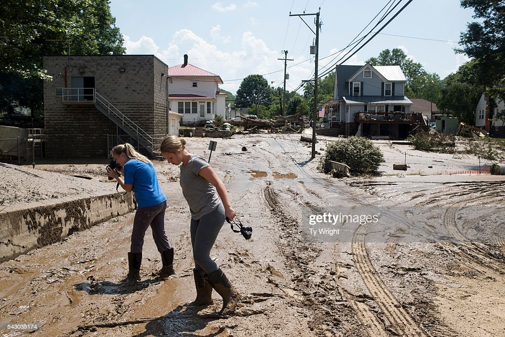 People take pictures of the mud covering the front of their home and a street intersection on June 25, 2016 in Clendenin, West Virginia. Bennett said they lost many of the belongings they had in the flood. The flooding of the Elk River claimed the lives of at least 23 people in West Virginia.