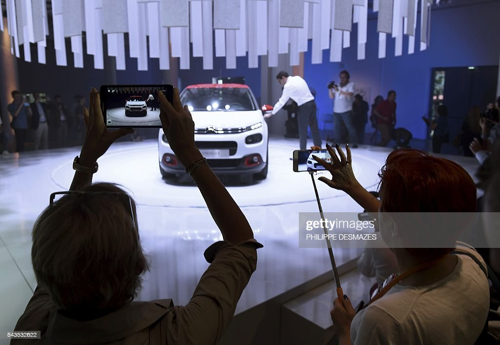 People take pictures of the new Citroen C3 during its unveiling in Lyon on June 29, 2016. / AFP / PHILIPPE