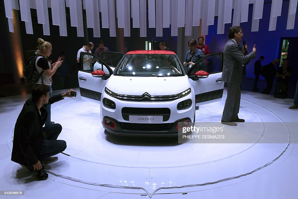 People take pictures of the new Citroen C3 of French automobile manufacturer, during its presentation in Lyon on June 29, 2016. / AFP / PHILIPPE