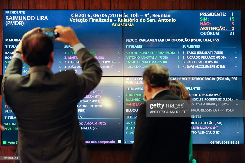 People take pictures of the panel showing the result of the Senate's Impeachment Special Committee against President Dilma Rousseff vote in Brasilia on May 6, 2016. A special committee in Brazil's Senate voted Friday to approve starting an impeachment trial against President Dilma Rousseff, who now faces being suspended from office in less than a week. The committee's recommendation was non-binding but marked the last formal stage before the full Senate votes Wednesday on whether to put the leftist leader on trial. Rousseff is accused of illegally manipulating government budget accounts. / AFP / ANDRESSA