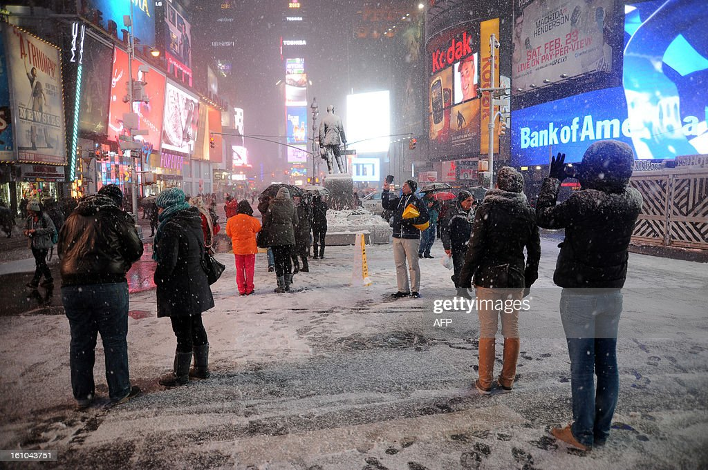 People take pictures of the snow in Times Square in New York on February 8, 2013 during a storm affecting the northeast US. The storm was forecast to bring the heaviest snow to the densely-populated northeast corridor so far this winter, threatening power and transport links for tens of millions of people and the major cities of Boston and New York. New York and other regional airports saw more than 4,500 cancellations ahead of what the National Weather Service called 'a major winter storm with blizzard conditions' along most of the region's coastline.
