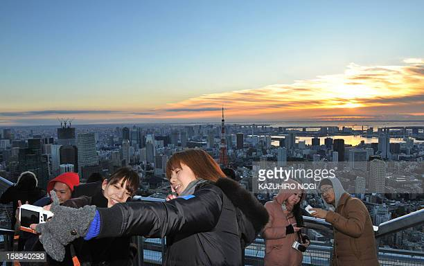 People take pictures of the sunrise on New Year's Day at the openair Sky Deck of Roppongi Hills some 238 metres above ground level in Tokyo on...