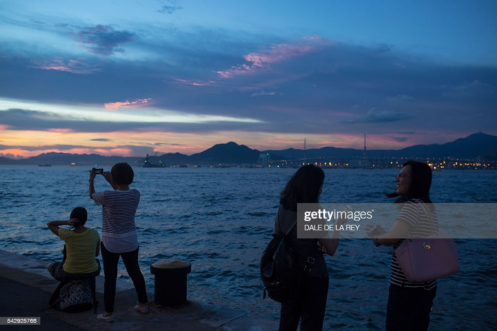 People take pictures of the sunset on a public pier in Hong Kong on June 25, 2016. / AFP / DALE
