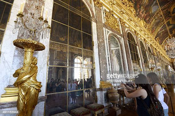People take pictures of their reflection in a mirror as they visit the Hall of Mirrors of the Chateau de Versailles on June 24 in Versailles France...