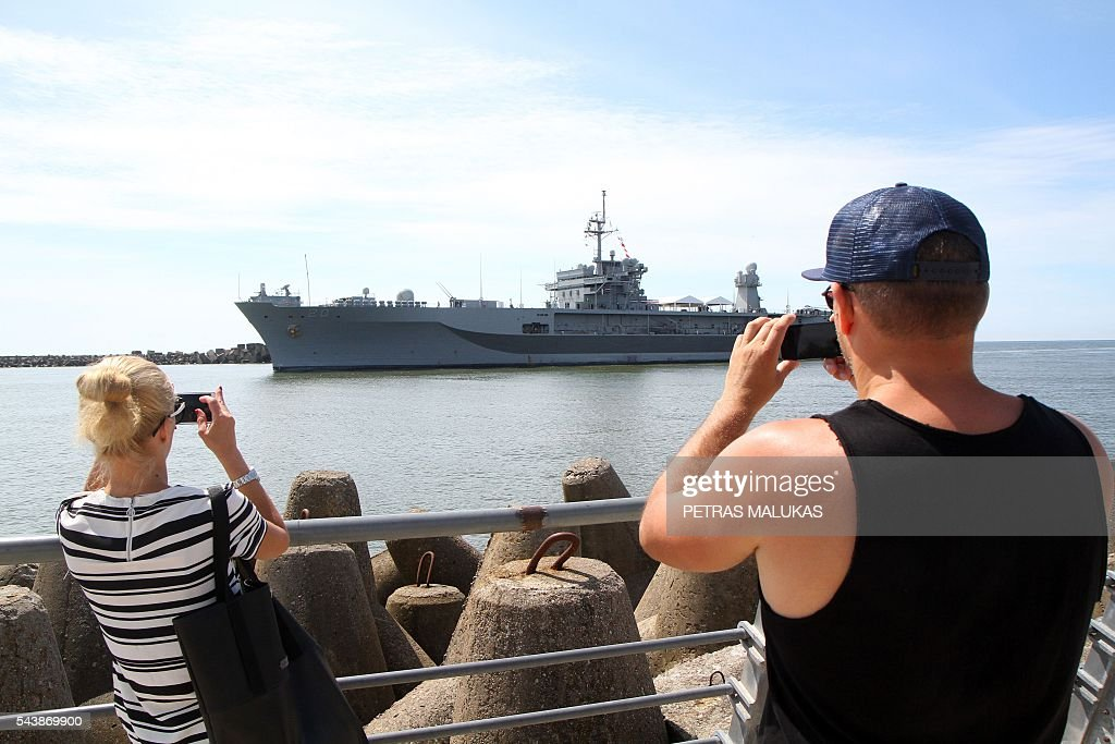 People take pictures of USS Mount Whitney, the flagship of the US Sixth Fleet, entering the port of Klaipeda on June 30, 2016. / AFP / Petras Malukas