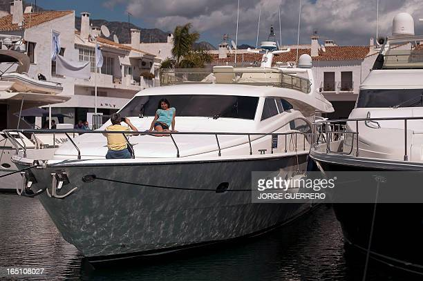 People take pictures on a yacht in Puerto Banus near Marbella on March 30 2013 AFP PHOTO / JORGE GUERRERO