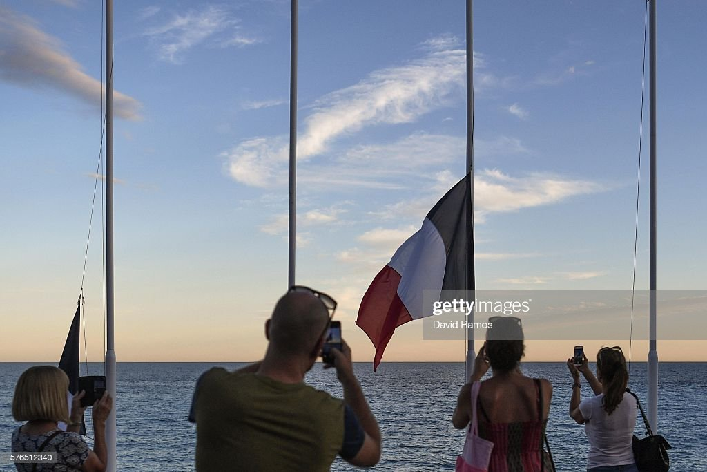 People take pictures to French flags flying at half mast on the Promenade des Anglais on July 15, 2016 in Nice, France. A French-Tunisian attacker killed 84 people as he drove a lorry through crowds, gathered to watch a firework display during Bastille Day Celebrations. The attacker then opened fire on people in the crowd before being shot dead by police.