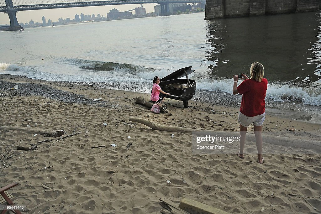 People take pictures with a piano underneath the Brooklyn Bridge on June 3, 2014 in New York City. A grand piano that has mysteriously landed on a sliver of beach under the iconic bridge last week has become an impromptu tourist attraction. While the Mason & Hamlin piano is badly damaged, dozens of people climb onto the beach daily to test out the keys.