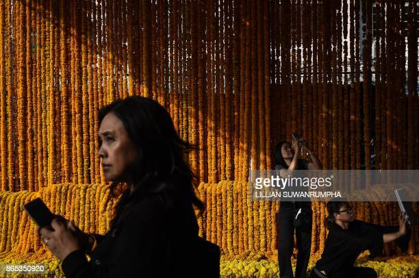 TOPSHOT People take pictures with elaborate floral displays made in honour of the late Thai king Bhumibol Adulyadej at Pak Khlong Talad flower market...