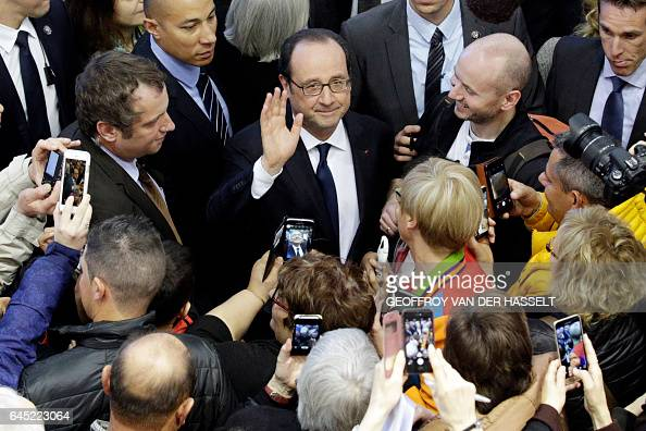 TOPSHOT People take pictures with their cellphones of French President Francois Hollande as he is followed by French Agriculture Minister and...