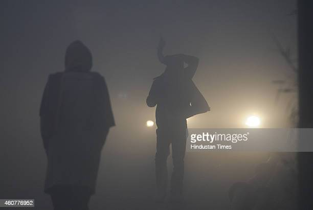 People take precautions against the cold weather in the foggy morning at Mayur Vihar on December 22 2014 in New Delhi India Dense fog reduced...