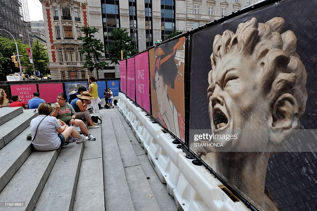 People take refuge in the shade on the steps of the Metropolitan Museum of Art on July 19, 2013 in New York as a heatwave continues in the northeast. Posters (R) are on a construction fence as renovations take place at the museum's entrance. AFP PHOTO/Stan HONDA
