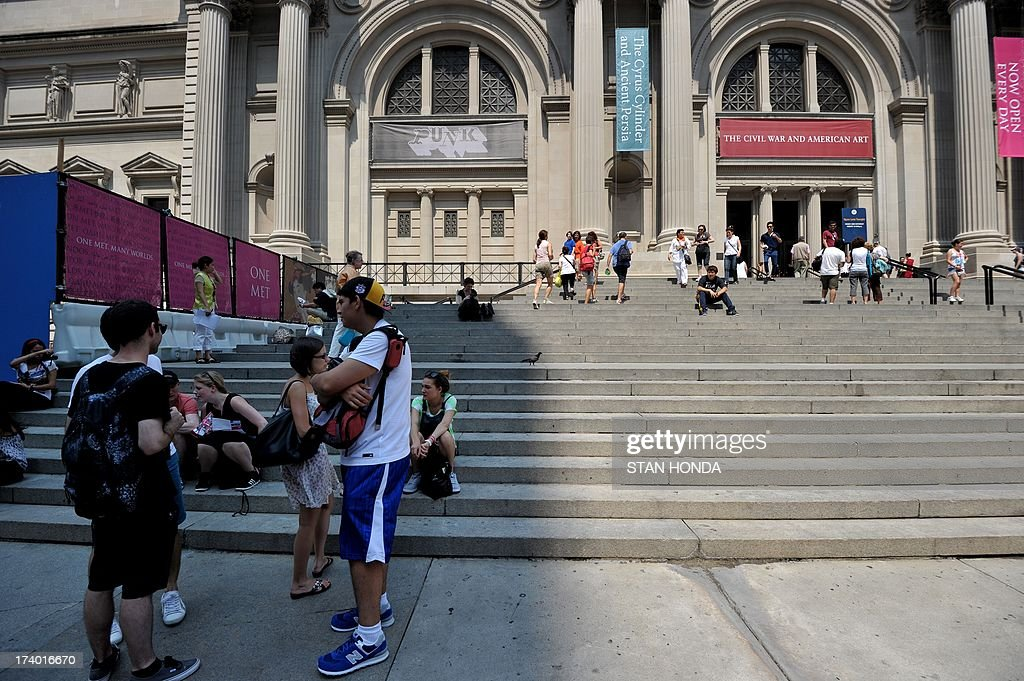 People take refuge in the shade on the steps of the Metropolitan Museum of Art on July 19, 2013 in New York as a heatwave continues in the northeast. AFP PHOTO/Stan HONDA