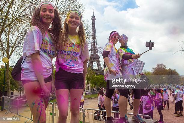 People take selfie during Color Run 2016 in Paris France on April 17 2016 People covered in colourful chalk powder dance at the finish line after...