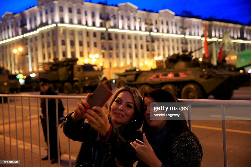 People take selfies as Russian military vehicles parade through the Red Square during the rehearsal of Russia's Victory Day (9 May) in Moscow, Russia on April 28, 2016.