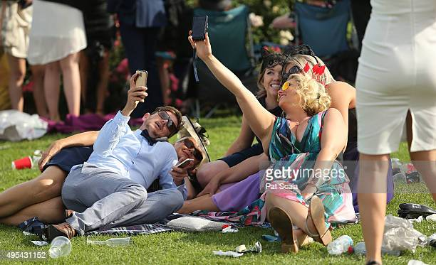 People take selfies as they attend the 2015 Melbourne Cup Day at Flemington Racecourse on November 3 2015 in Melbourne Australia