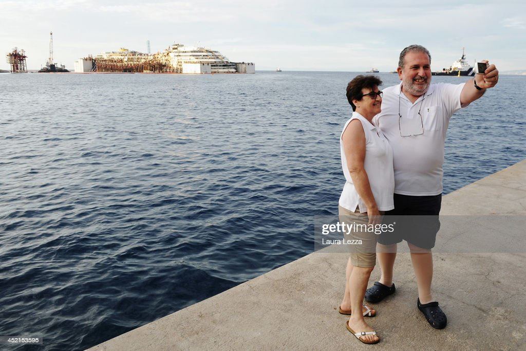 People take selfies near the wrecked ship Costa Concordia after the succesfull refloating operations on July 14, 2014 in Isola del Giglio, Italy. On the first day of the operation the wreck will be partially refloated by 2 metres from the platfoms that support it and will be moved approximately 30 metres to the east. The wreck will then be kept in position by tugs and moored by anchors aft, with steel cables. The refloating operation is expected to take up to a week before being towed to the port of Genoa for dismantling.