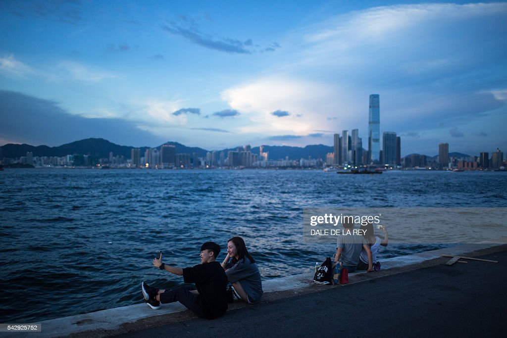 People take selfies on a public pier in Hong Kong on June 25, 2016. / AFP / DALE