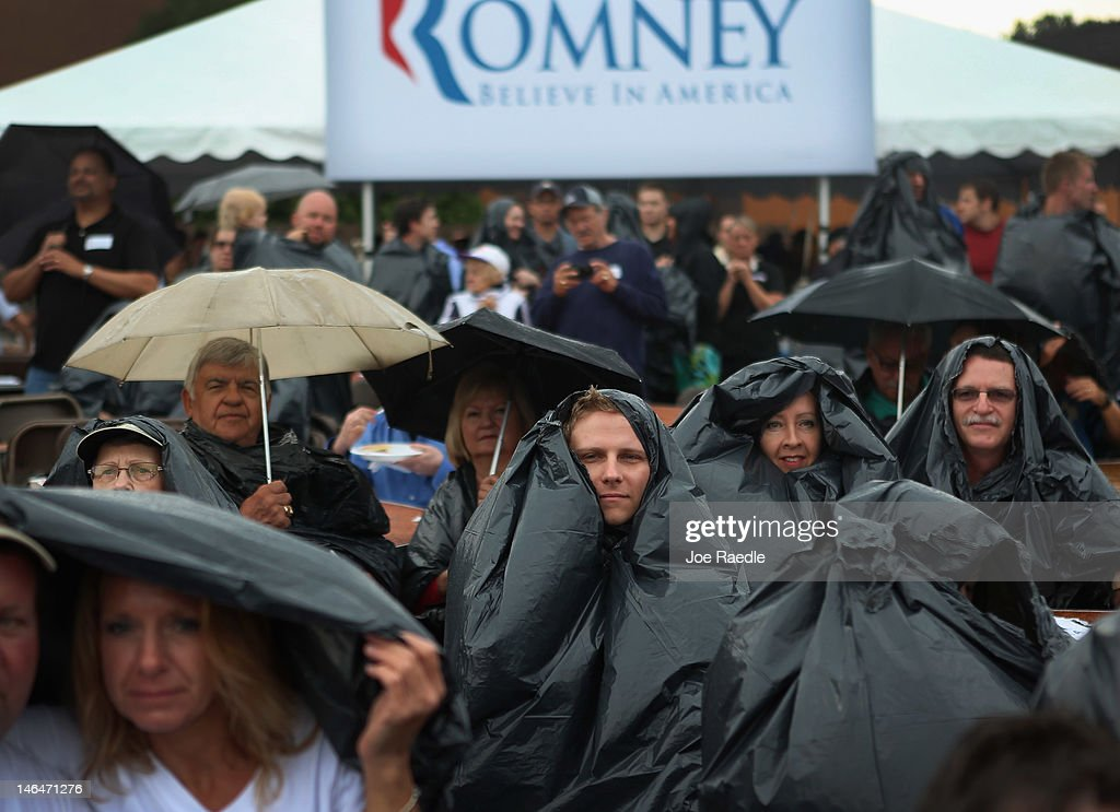 People take shelter from a downpour under garbage bags as they wait for the arrival of Republican Presidential candidate, former Massachusetts Governor Mitt Romney during a pancake breakfast campaign stop at Mapleside Farms on June 17, 2012 in Brunswick, Ohio. Romney is on a campaign swing through battleground states.