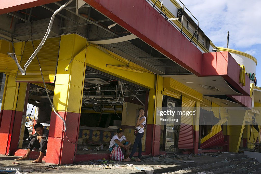People take shelter from the sun inside a damaged McDonald's Corp. fast-food restaurant in Tacloban, the Philippines, on Monday, Nov. 18, 2013. Super Typhoon Haiyan slammed into the central Philippines on Nov. 8, knocking down most buildings, killing thousands, displacing 4 million people and affecting more than 10 million. Photographer: Paula Bronstein/Bloomberg via Getty Images