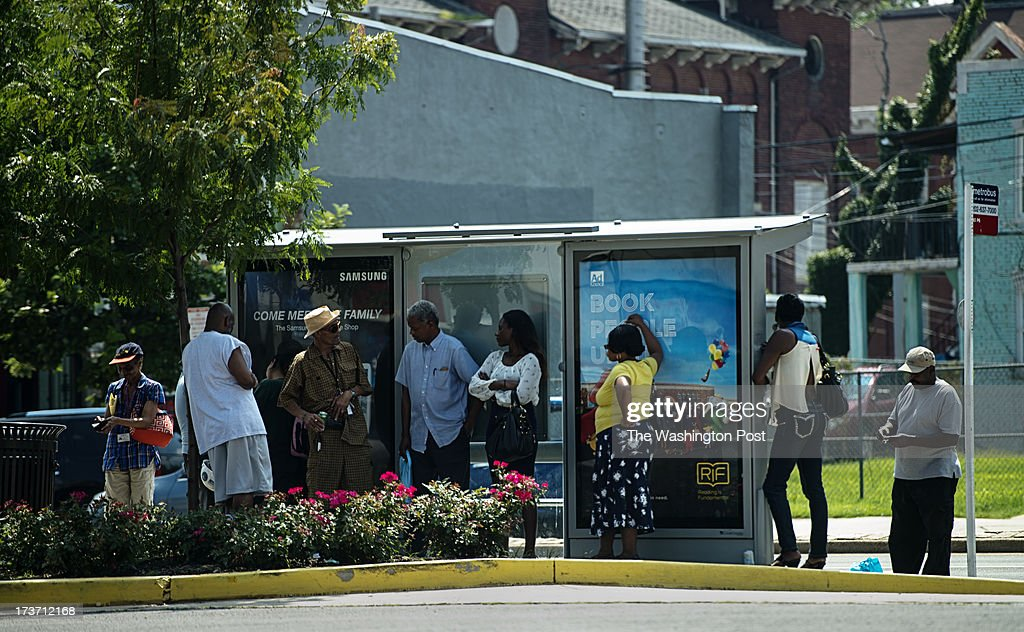 People take shelter from the toasty temperatures in the shade while they wait for the metro bus at the intersection of North Capitol and Florid...